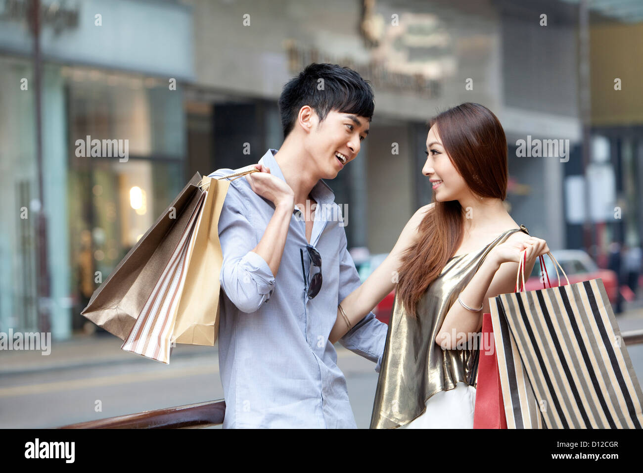 Happy young couple looking into each other's eyes tenderly in the street, Hong Kong - Stock Image