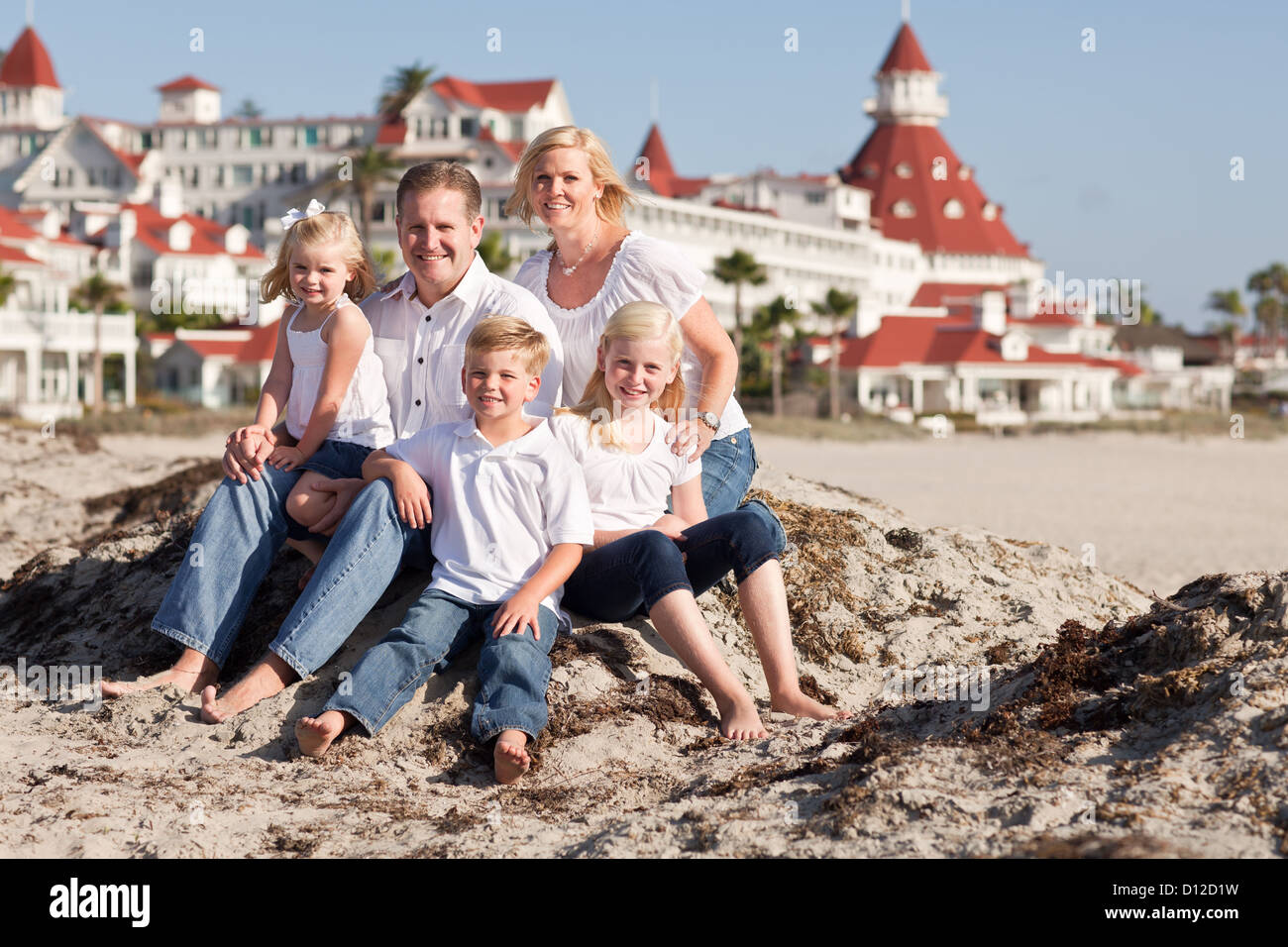 Happy Caucasian Family in Front of Hotel Del Coronado, U.S.A., on a Sunny Afternoon. Stock Photo