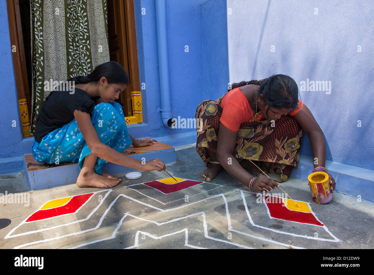Young Indian Woman And Teenage Girl Painting A Rangoli Design