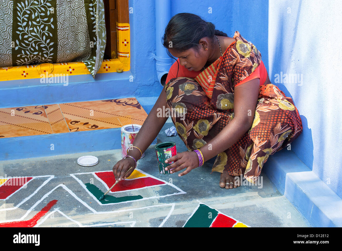Young Indian Woman Painting A Rangoli Design Outside A Rural Indian