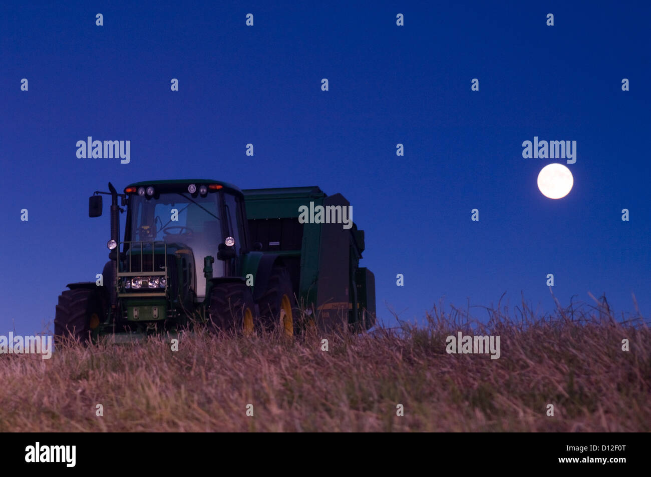 Tractor and Baler under Full Moon.  South-western Alberta outside Pincher Creek. Canada. - Stock Image