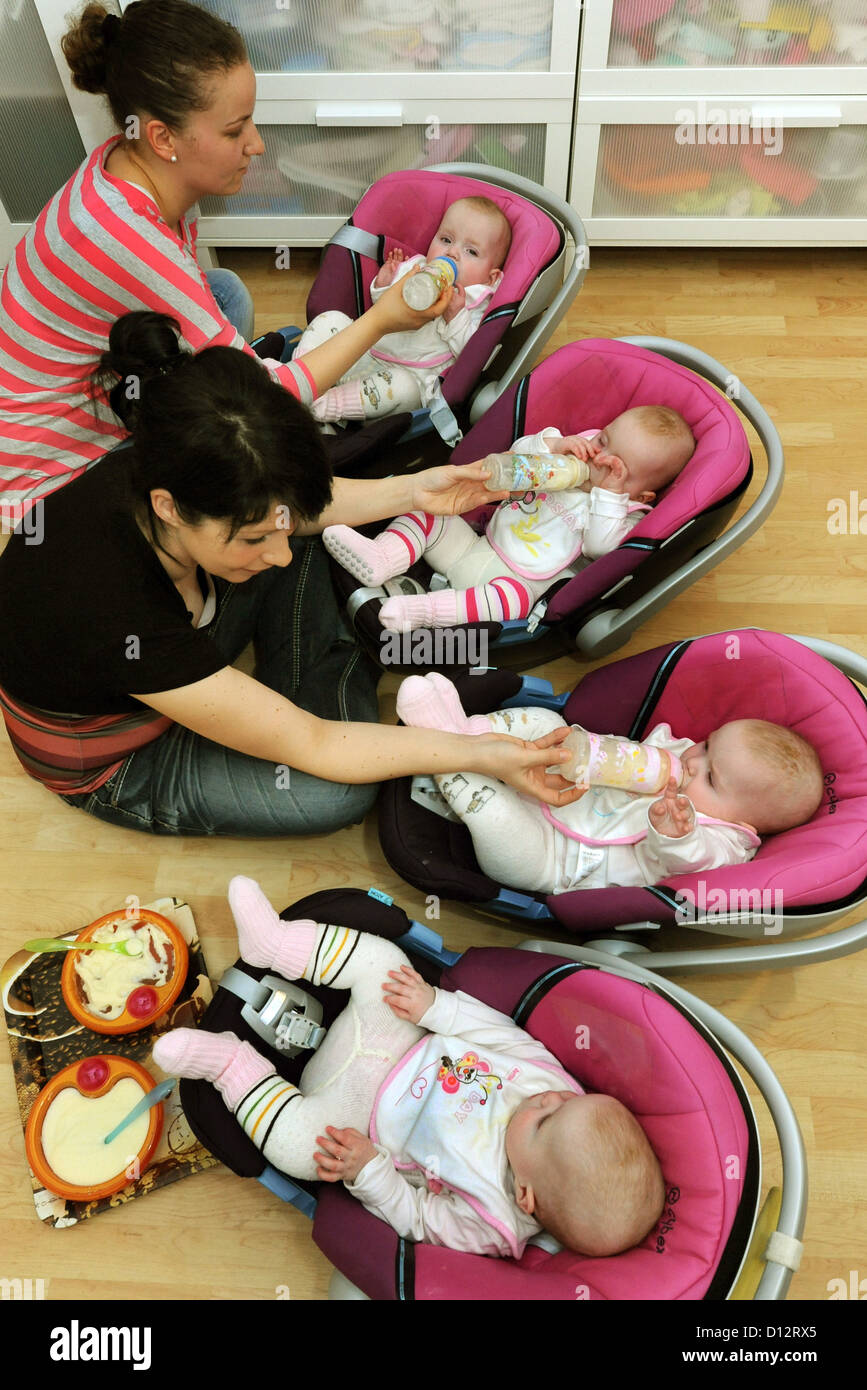 Mother Janett Mehnert and midwife Vivien Baum (in the back) feed the quadruplet sisters Jasmin, Kim, Laura and Sophie - Stock Image