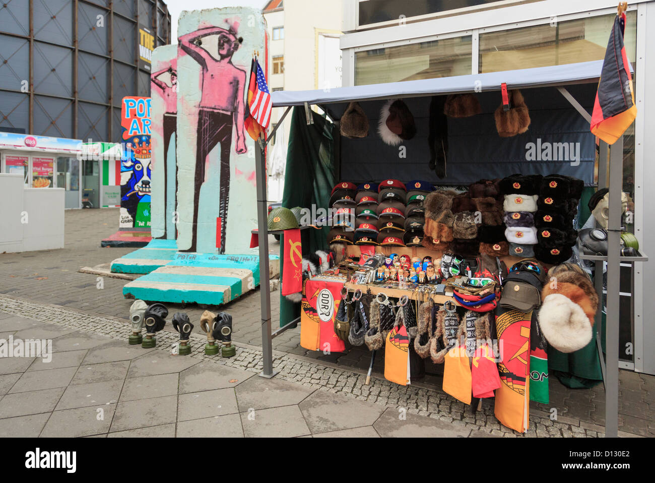 Stall selling DDR army and war memorabilia as souvenirs near sections of the original wall on Friedrichstrasse, - Stock Image