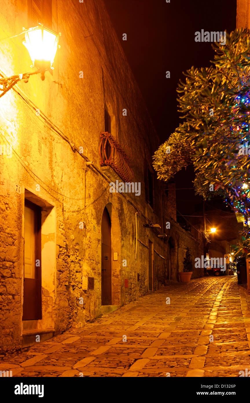 Cobblestone street illuminated by light at night. - Stock Image