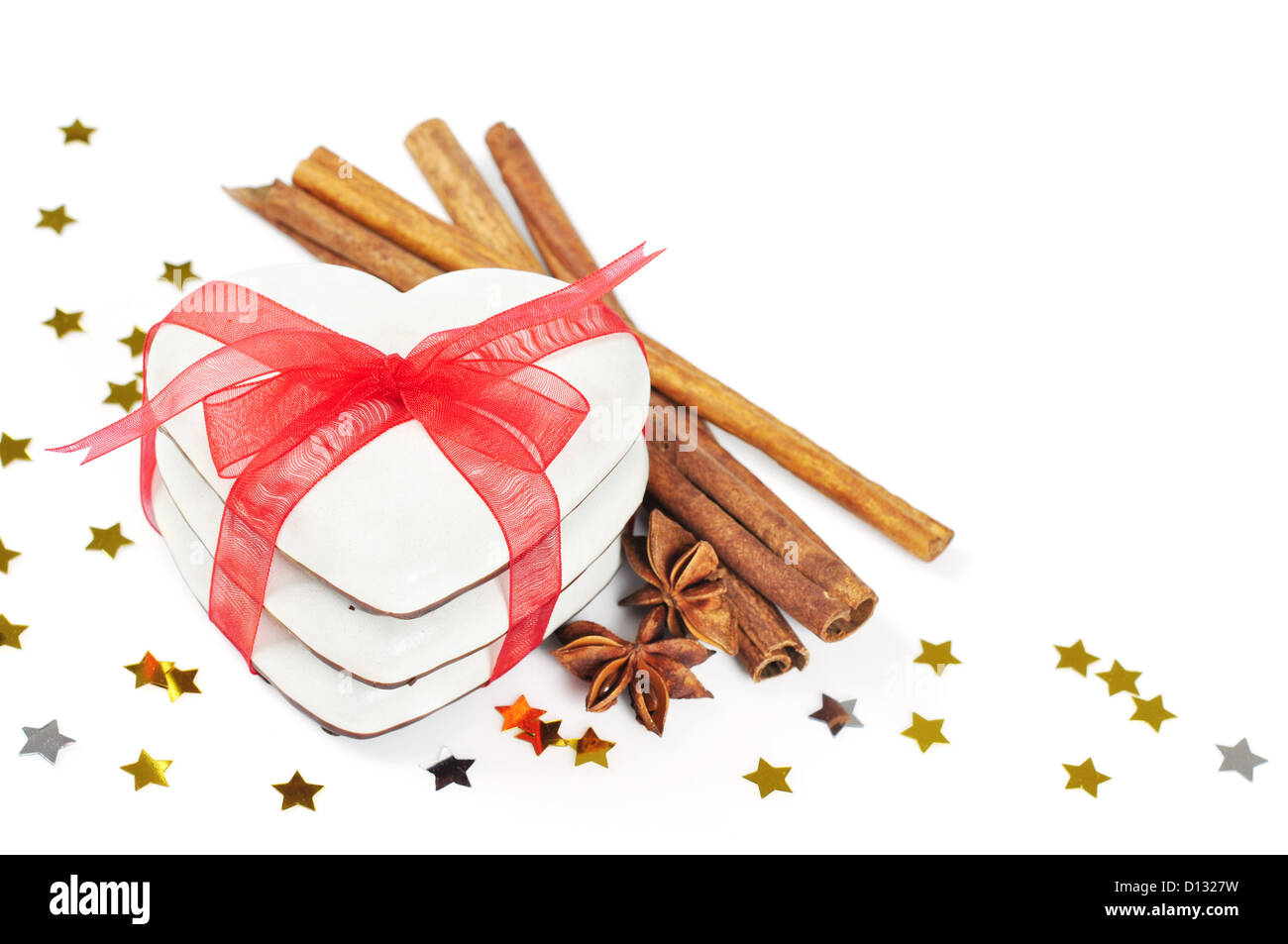 Gingerbread cookies with red ribbon and cinnamon isolated on white background - Stock Image