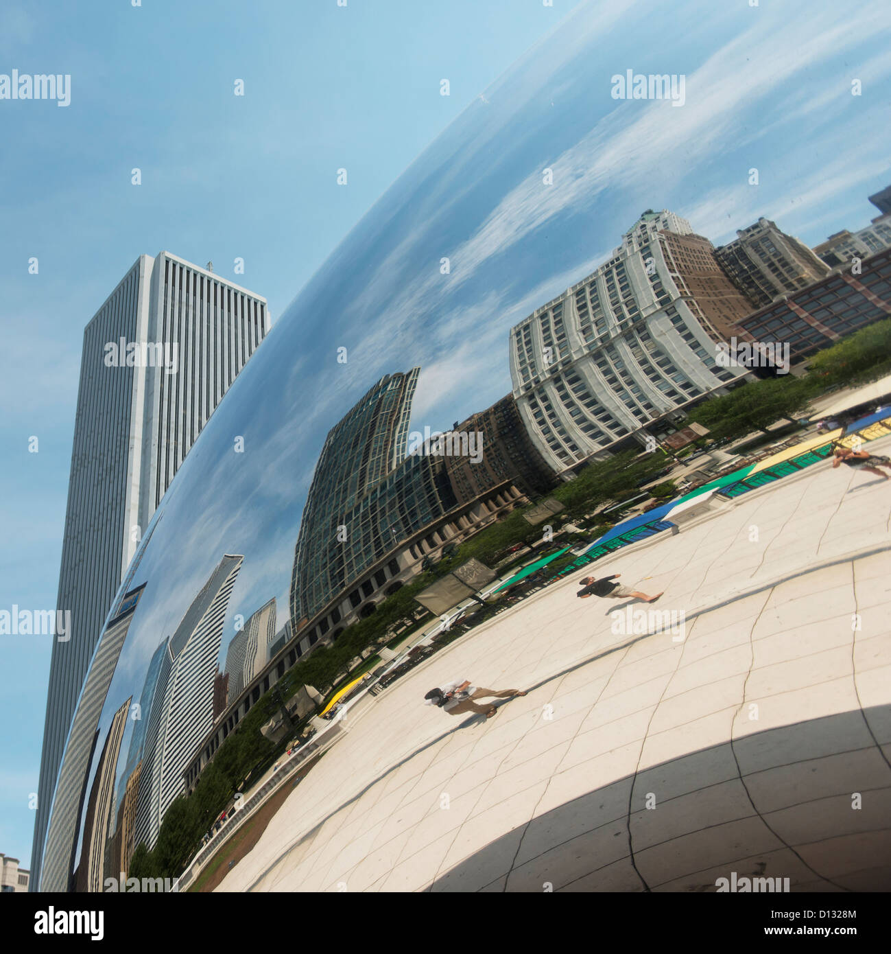 buildings and pedestrians reflected in a silver rounded sculpture