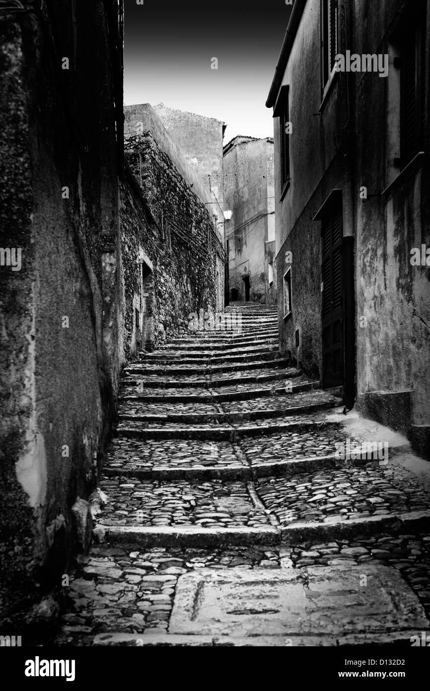 Narrow cobblestone stairs illuminated by moonlight - Stock Image