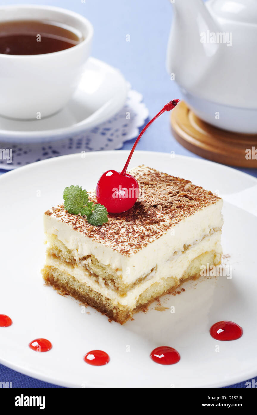 Tiramisu - Classical Dessert with Coffee on white plate. Garnished with Cherry and Mint. - Stock Image