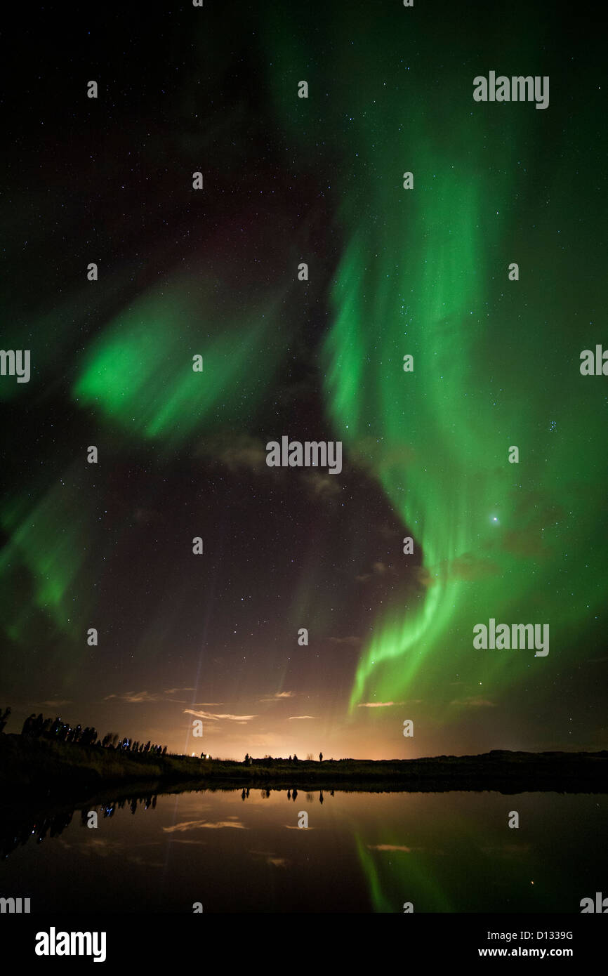 Aurora Borealis (Northern Lights) in Iceland near Reykjavik reflected in a pond with bystanders along the bank. Stock Photo