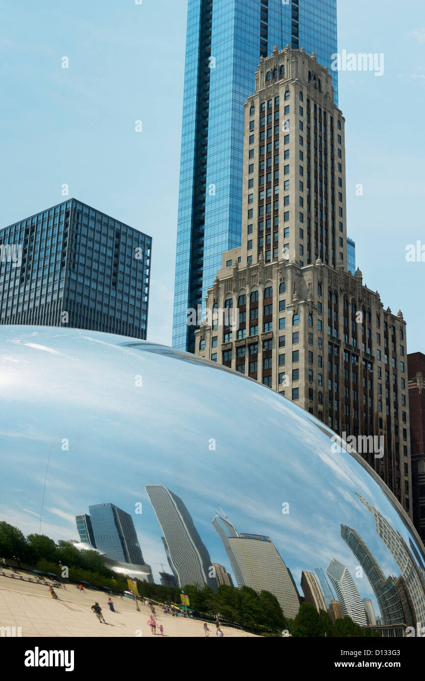 rounded silver sculpture reflecting pedestrians and buildings with