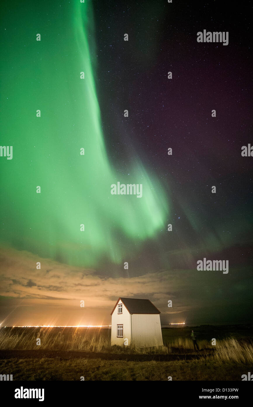 Green streaks of the Aurora Borealis Northern Lights over a small house in a field in iceland - Stock Image