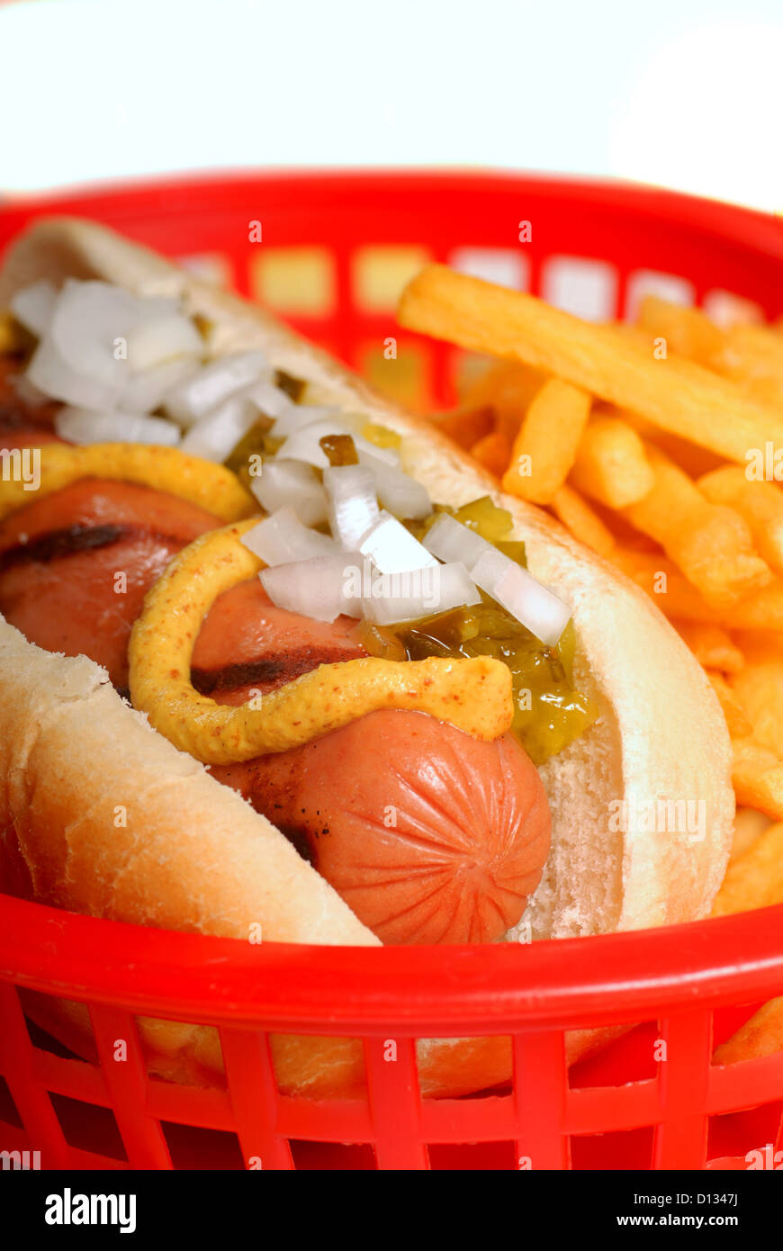Freshly grilled hot dog in a basket with french fries Stock Photo