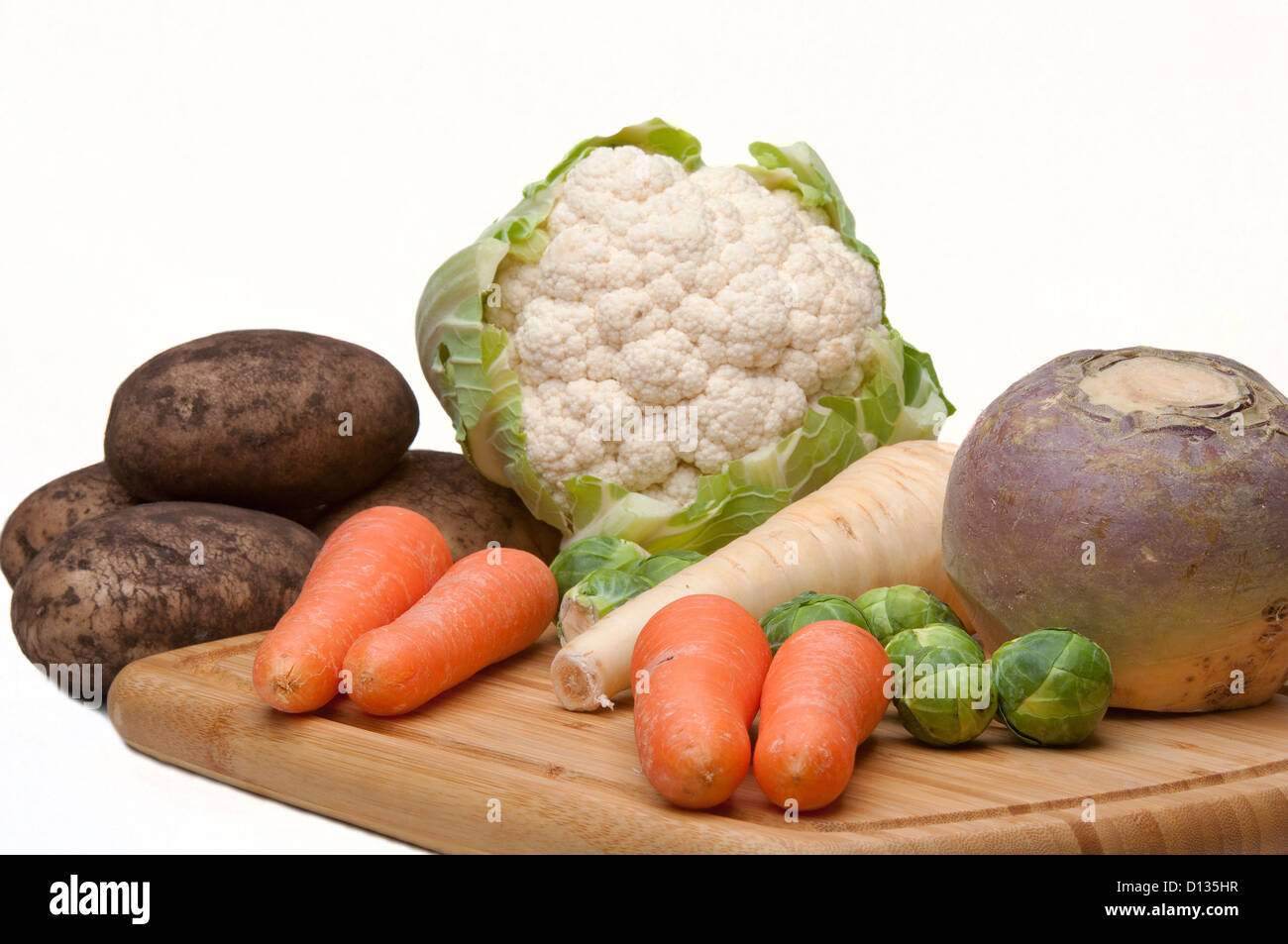 A selection of winter vegetables including swede,parsnip,carrots, brussel, potatoes and cauliflower on a white background - Stock Image