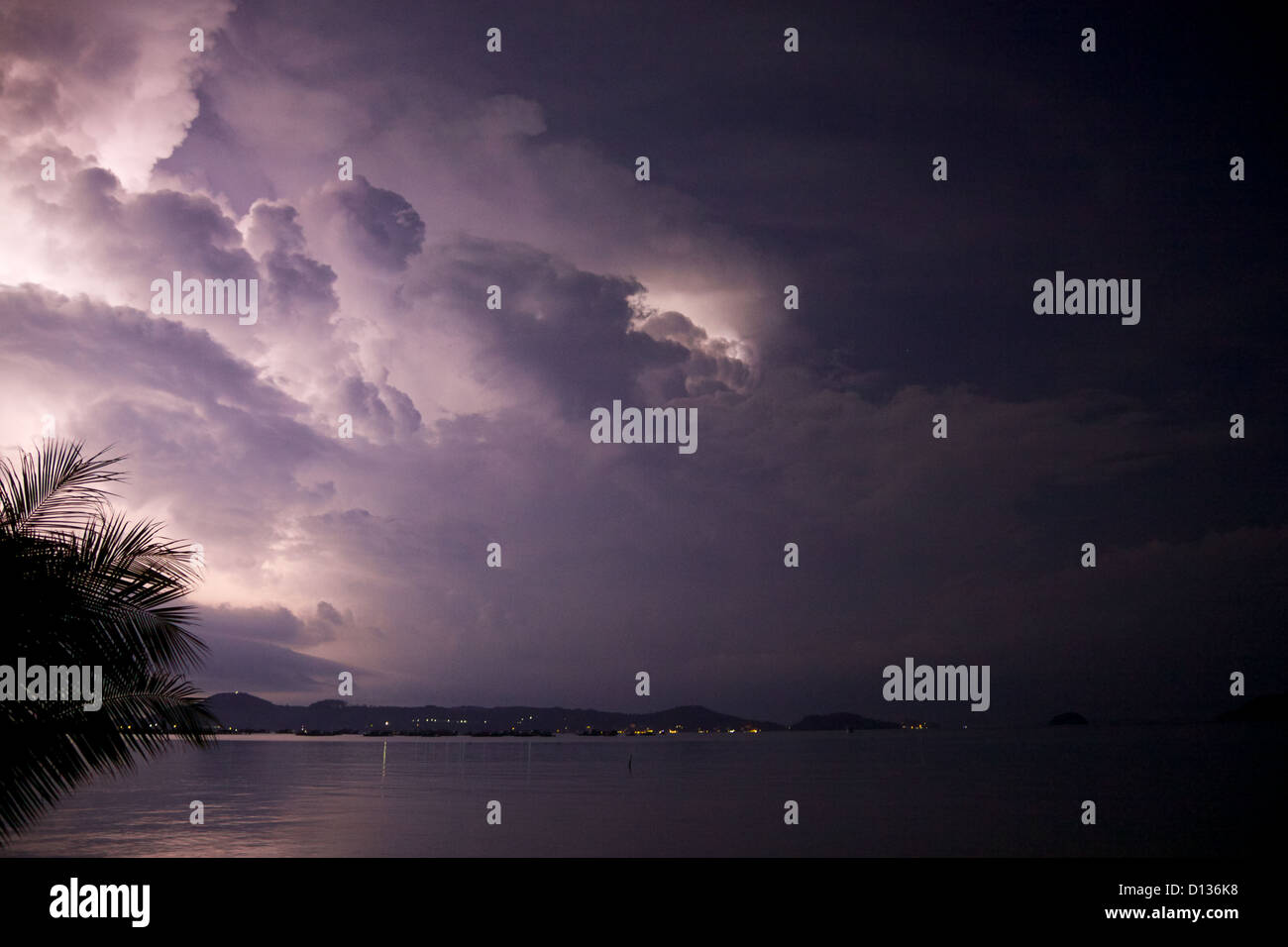Lightening behind the clouds at night,  Chalong bay, Phuket ,Thailand - Stock Image