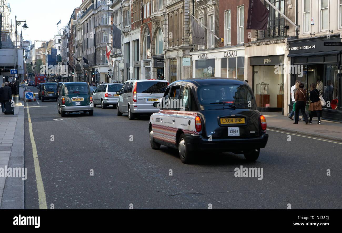 London, United Kingdom, traffic and prestigious boutiques in New Bond Street - Stock Image