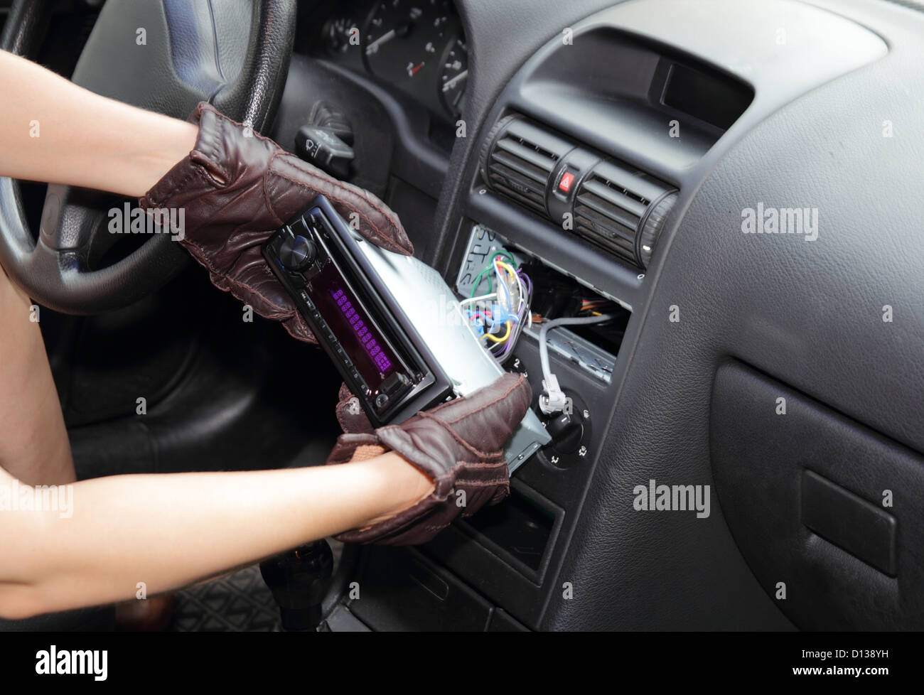 Gloved hands of a thief stealing a car radio from the dashboard of a car with the wiring exposed - Stock Image