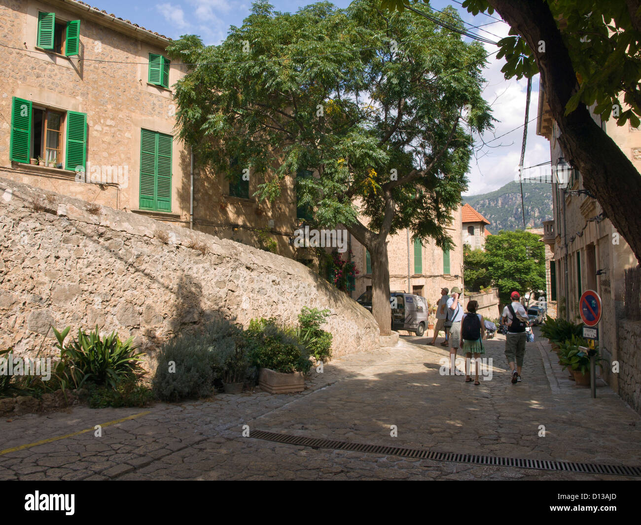 a street with  terracotta coloured stone houses and tourists  in Valldemossa / Valldemosa Majorca Stock Photo