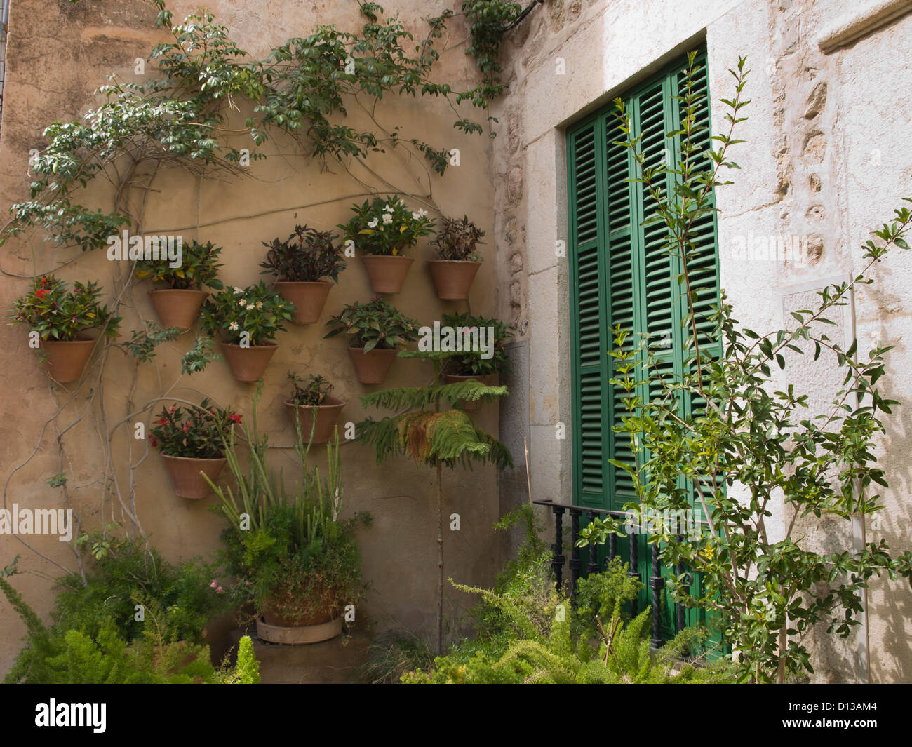 Green French balcony doors, potted plants on wall, a terracotta coloured house in Valldemossa / Valldemosa Majorca - Stock Image