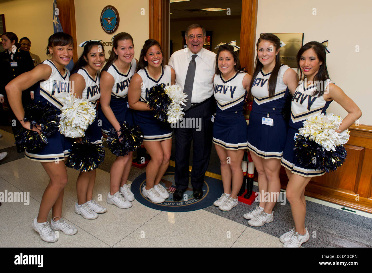 US Secretary of Defense Leon Panetta poses with the US Naval Academy Midshipmen cheerleaders during a pep rally - Stock Image