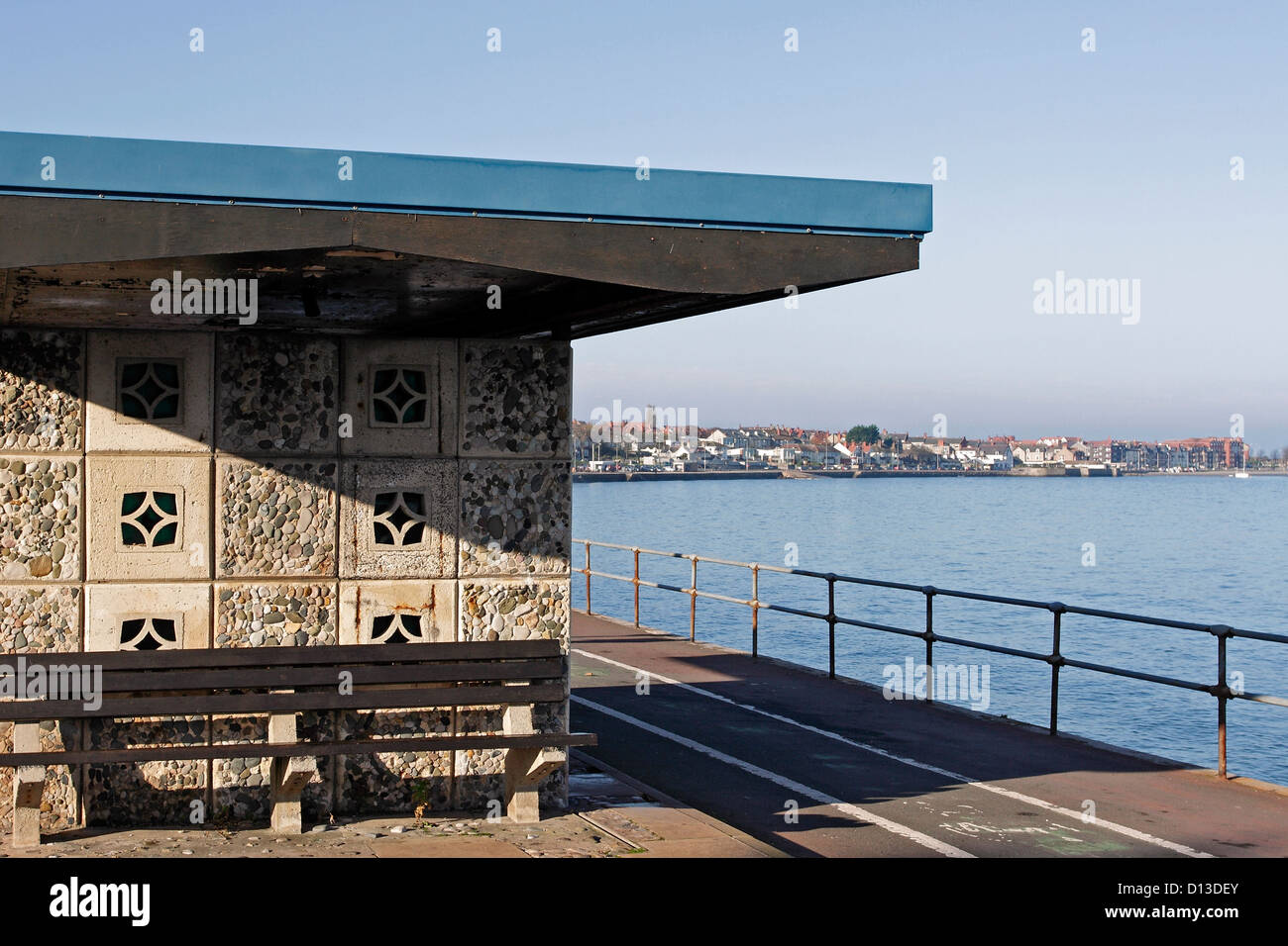 A seaside seating shelter on the promenade in Colwyn Bay, North Wales with Rhos on Sea visible in the distance. - Stock Image