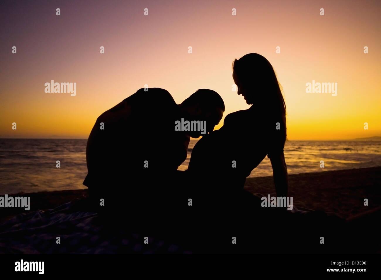 Silhouette Of Pregnant Couple On Beach At Sunset; Huntington Beach California Usa - Stock Image