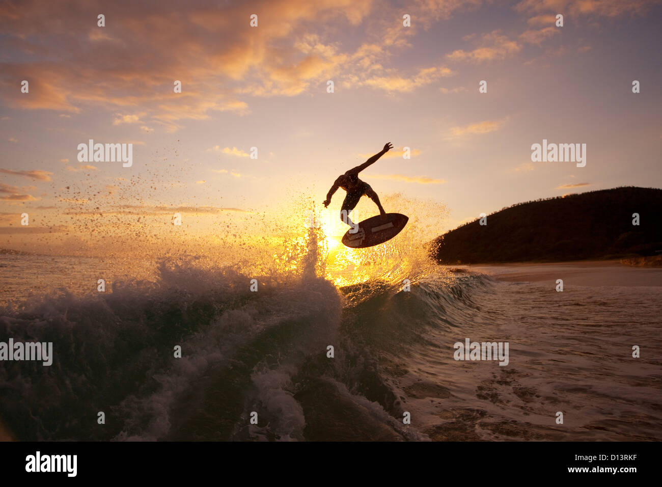 Hawaii, Maui, Makena, Skimboarder Gets Big Air Off A Wave At Sunset - Stock Image