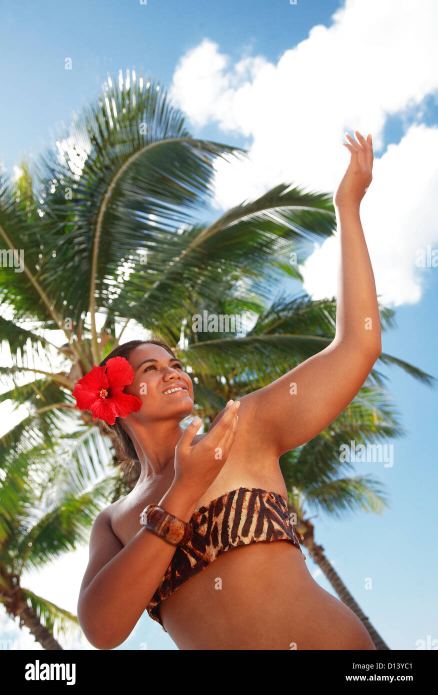 Hawaii, Oahu, Local Polynesian Hula Dancer Smiling And Dancing With Coconut Palm Trees In Background. - Stock Image