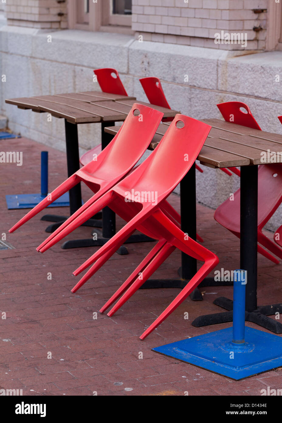 Red chairs leaning on tables - Stock Image