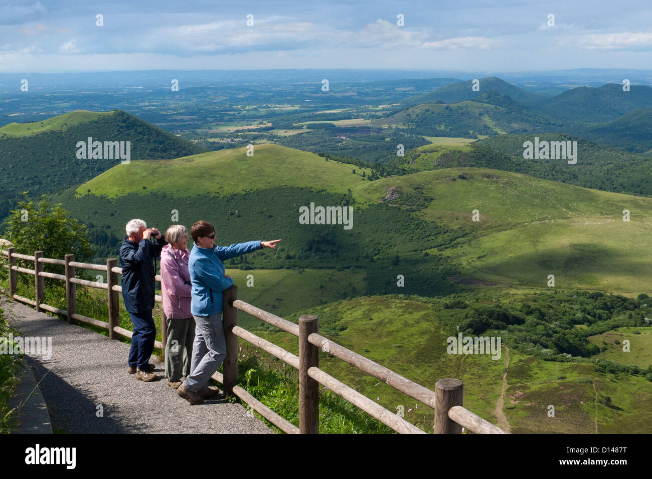 Tourists looking out from the top of the Puy de Dome to the volcanic region of the Puy de Dome in Auvergne, France - Stock Image