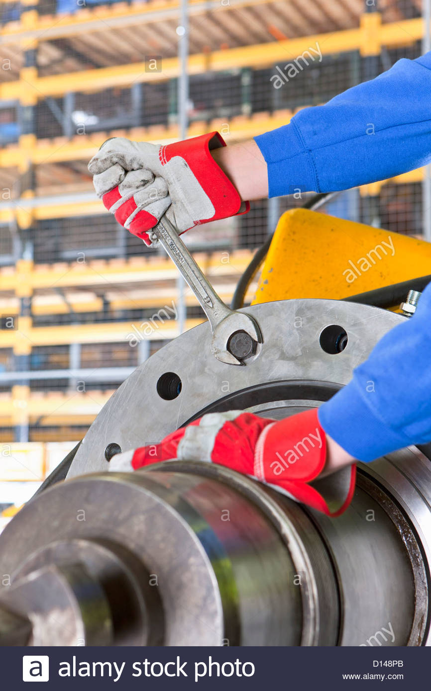 Close up of engineer tightening bolt on gearbox casing in factory - Stock Image