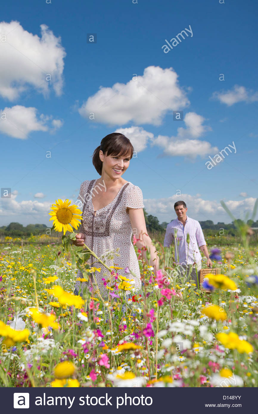 Smiling couple among wildflowers in sunny meadow - Stock Image