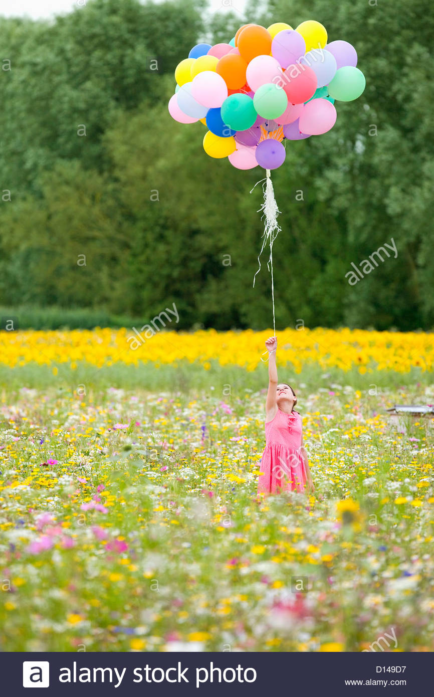 Girl holding bunch of balloons among wildflowers in sunny meadow - Stock Image