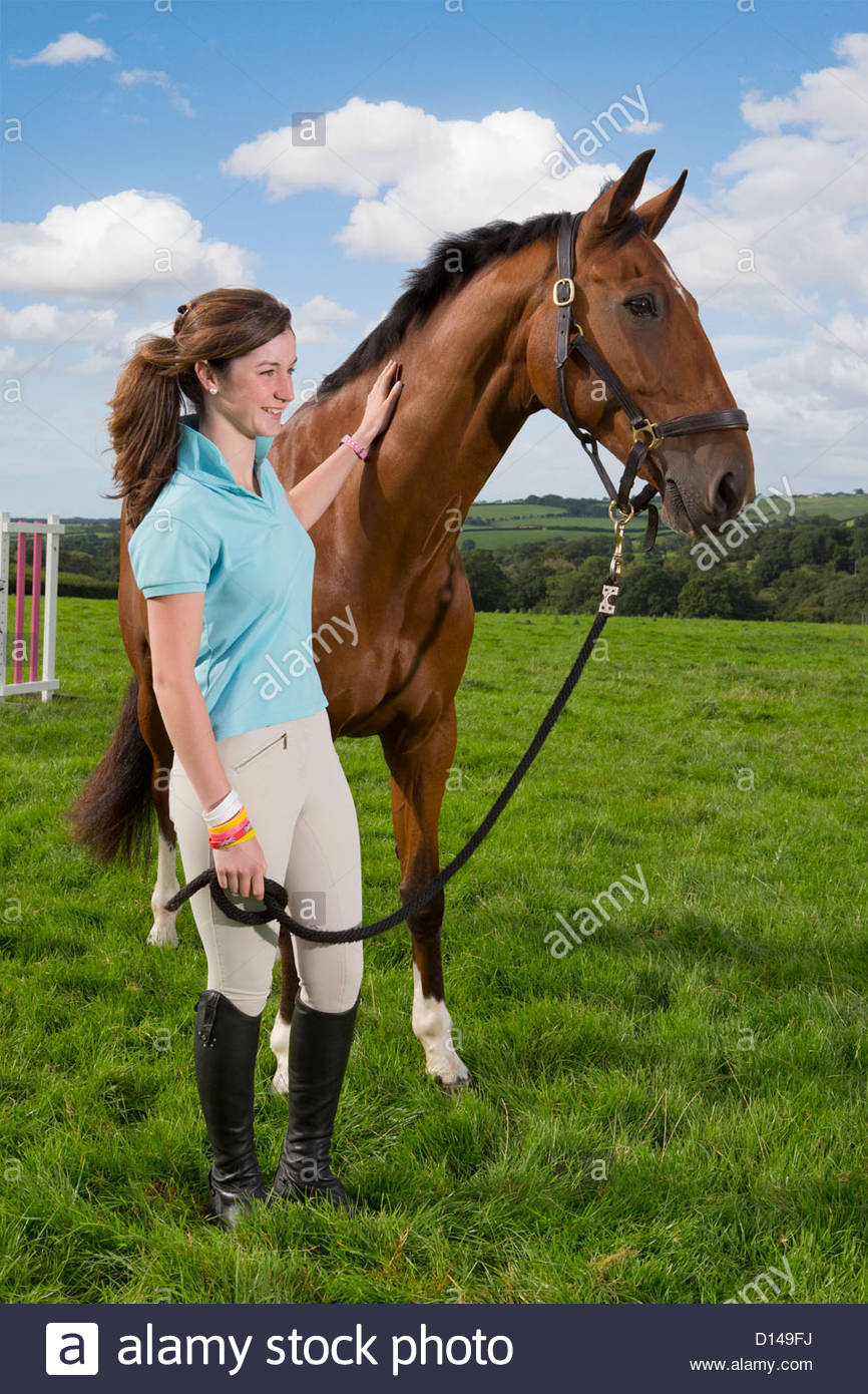 Smiling girl with horse in field - Stock Image