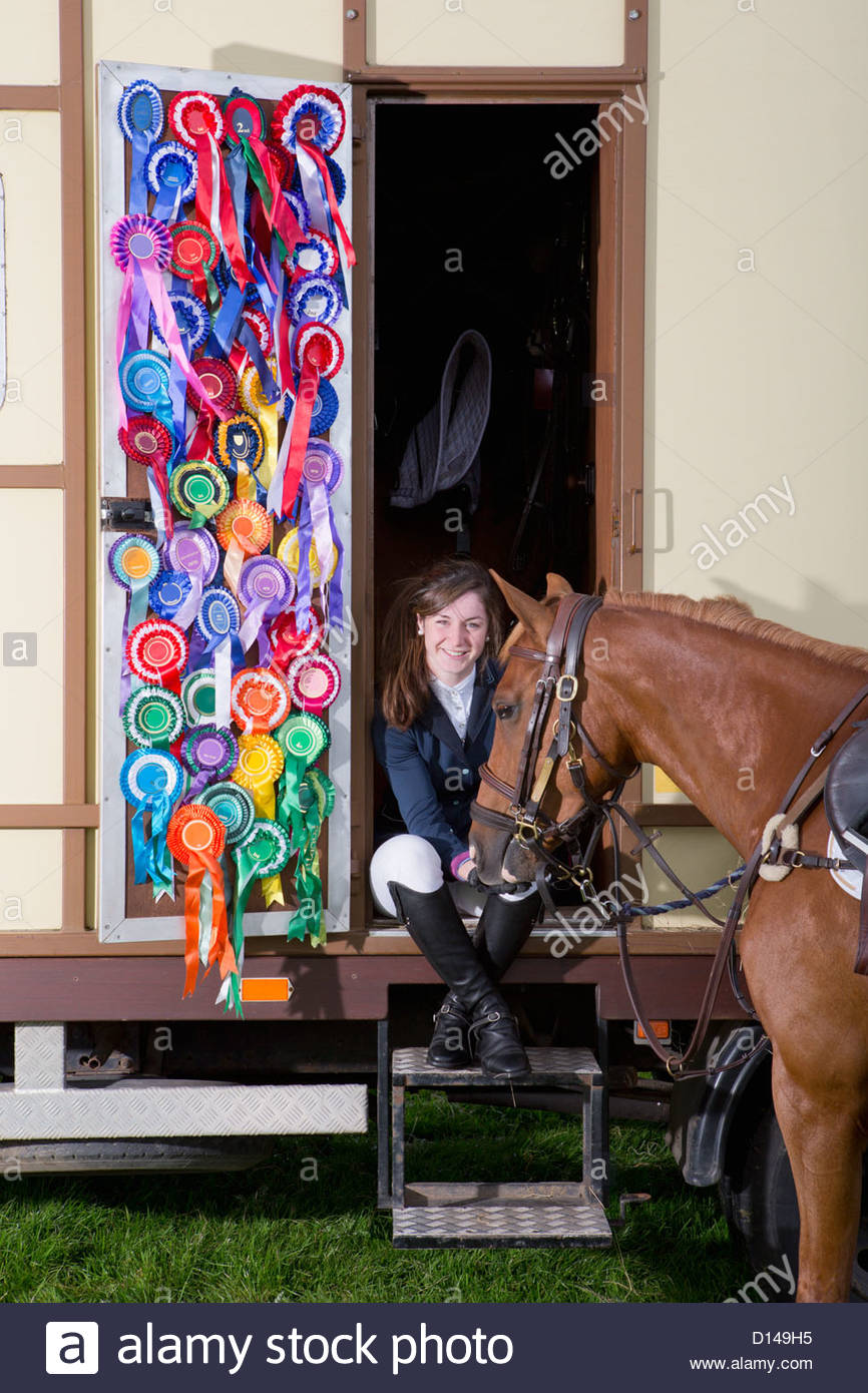 Portrait of smiling girl in equestrian uniform with horse in doorway of trailer with rosettes covering door - Stock Image
