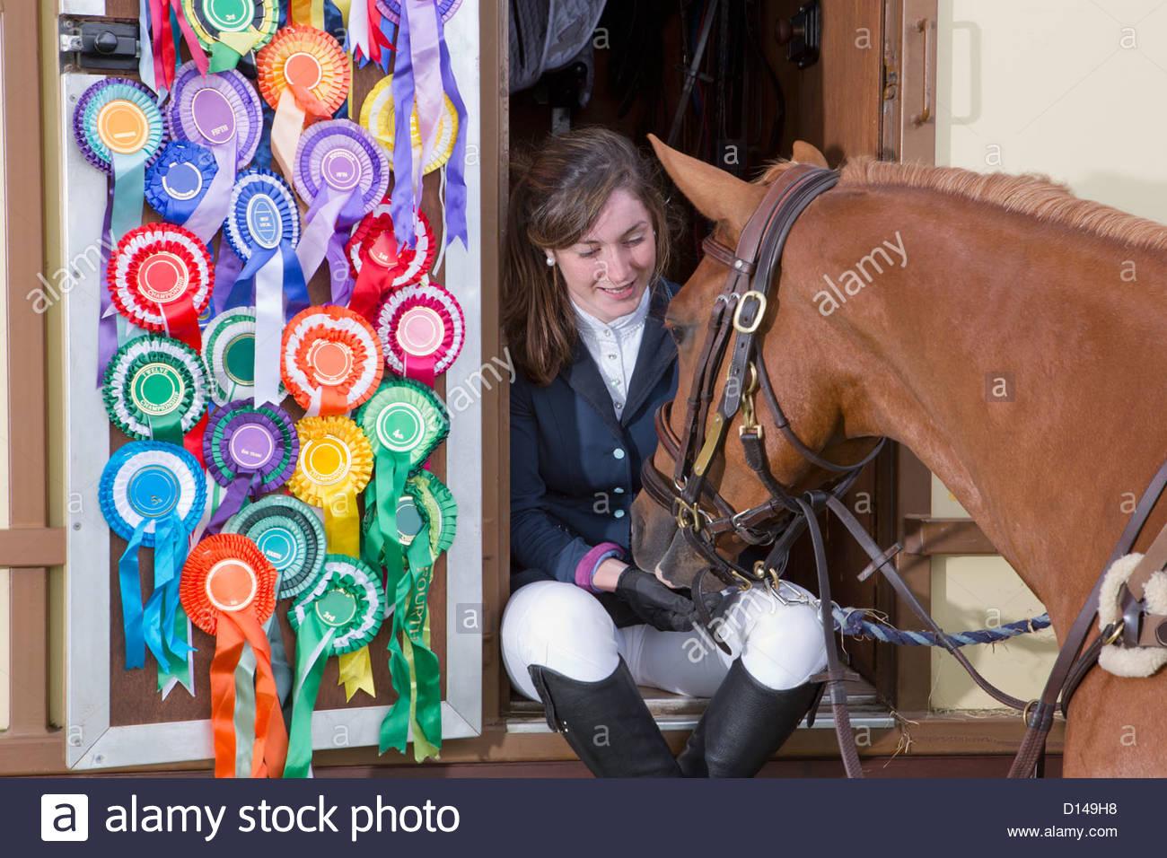 Girl in equestrian uniform feeding horse in doorway of trailer with rosettes covering door - Stock Image