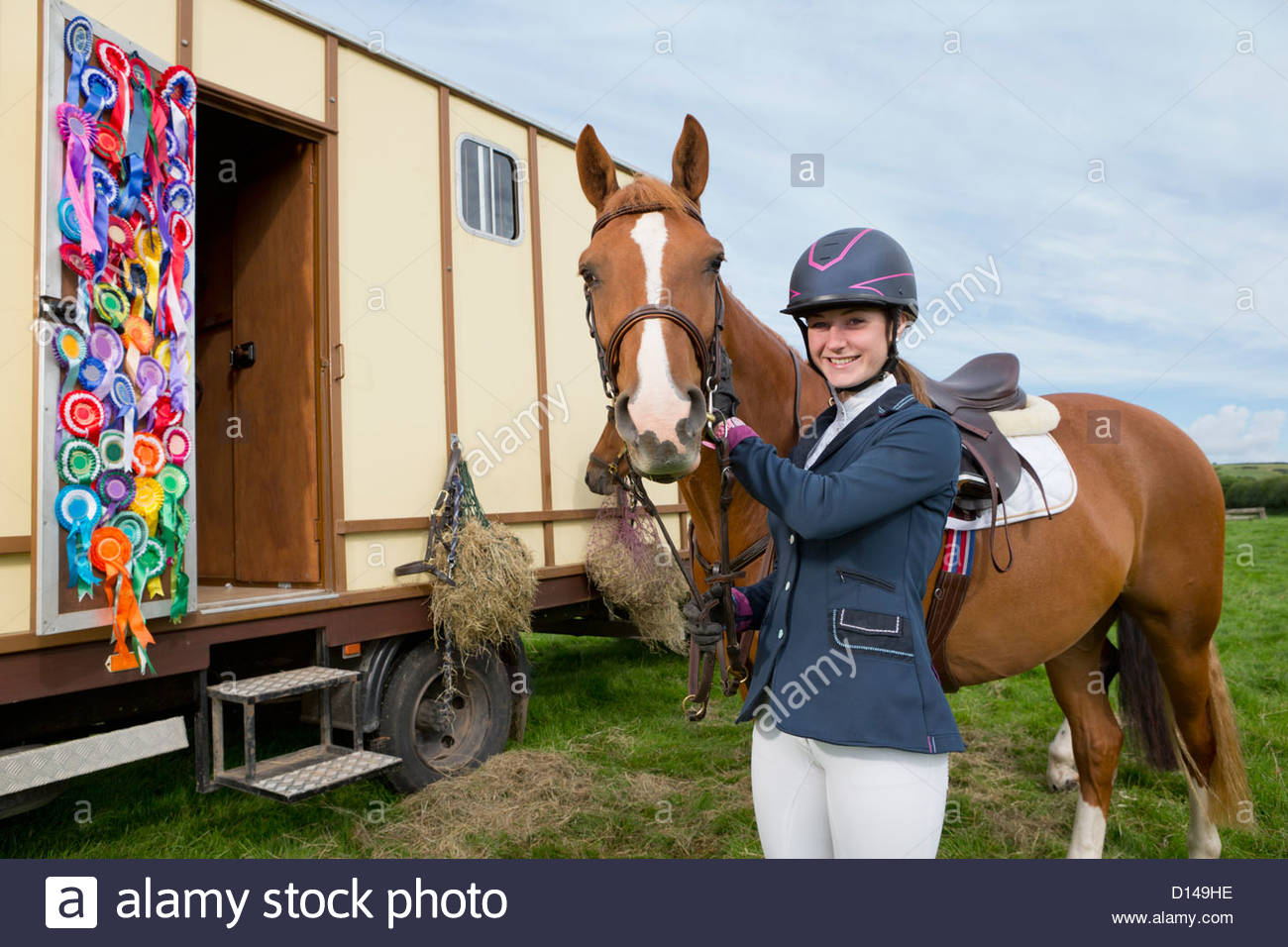Portrait of smiling girl in equestrian uniform with horse near trailer door covered with rosettes - Stock Image