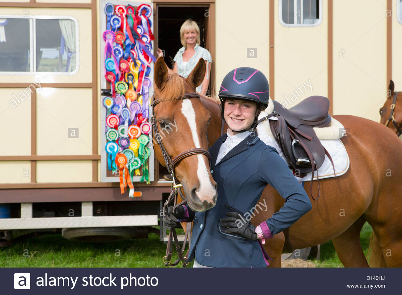 Portrait of smiling girl in equestrian uniform and horse near trailer with rosettes - Stock Image