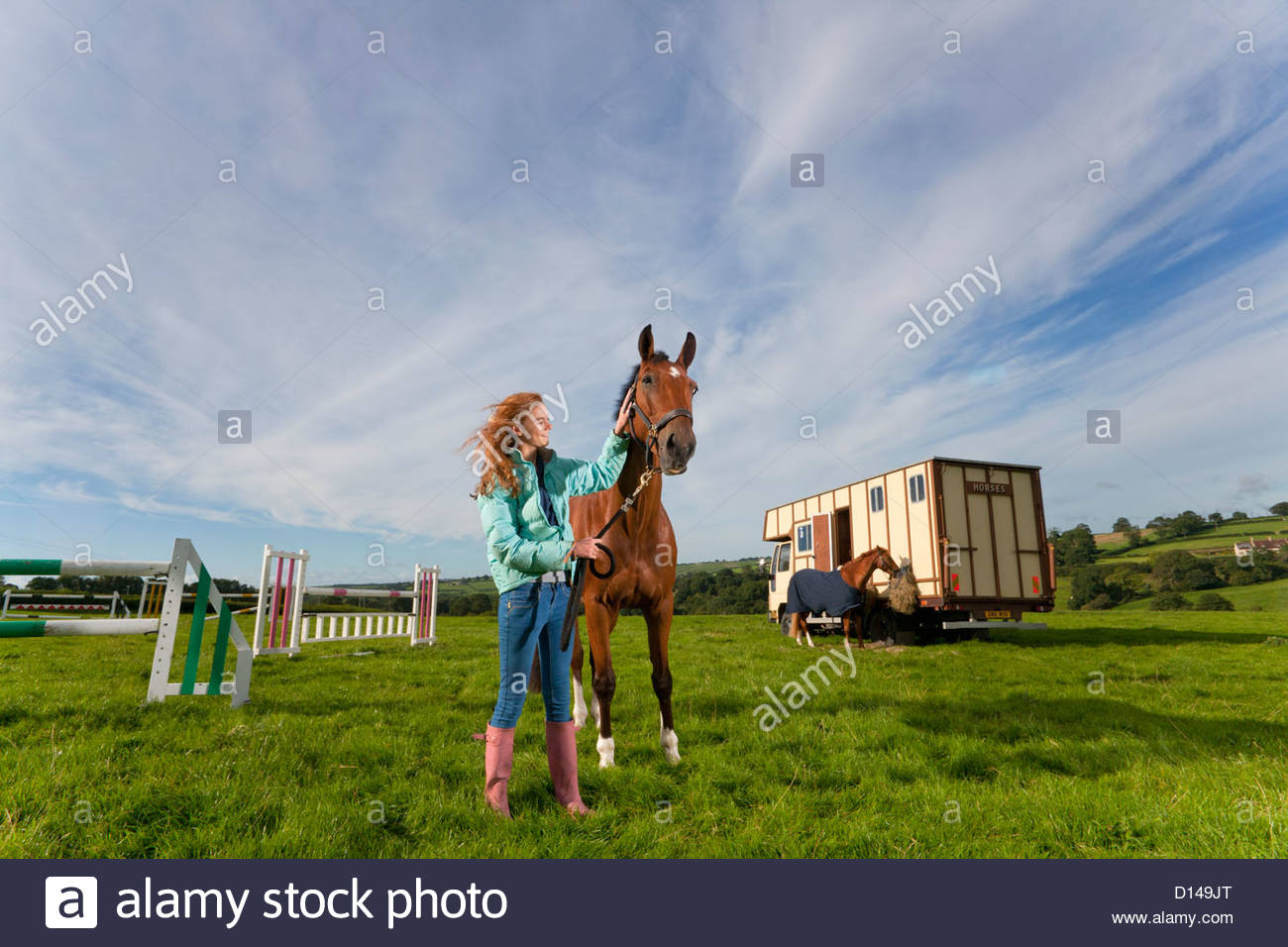 Girl with horse in field near trailer - Stock Image