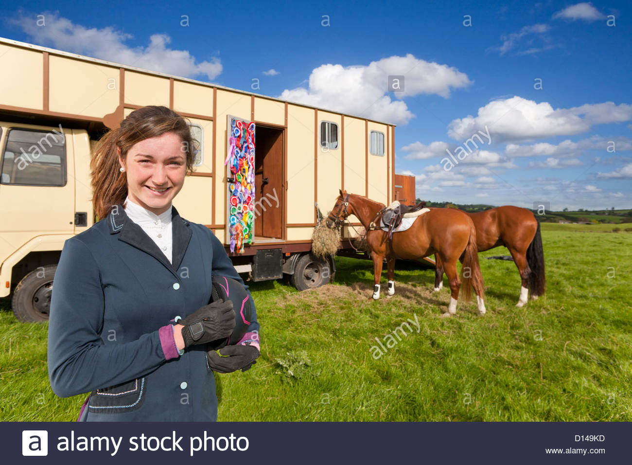 Portrait of smiling girl in equestrian uniform near horses and trailer in field - Stock Image
