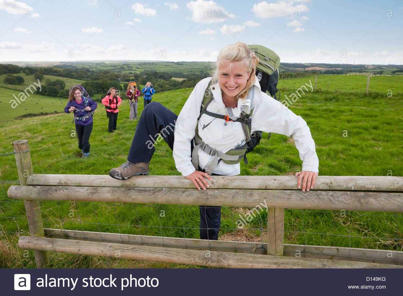 Smiling girl with backpack climbing fence in field - Stock Image