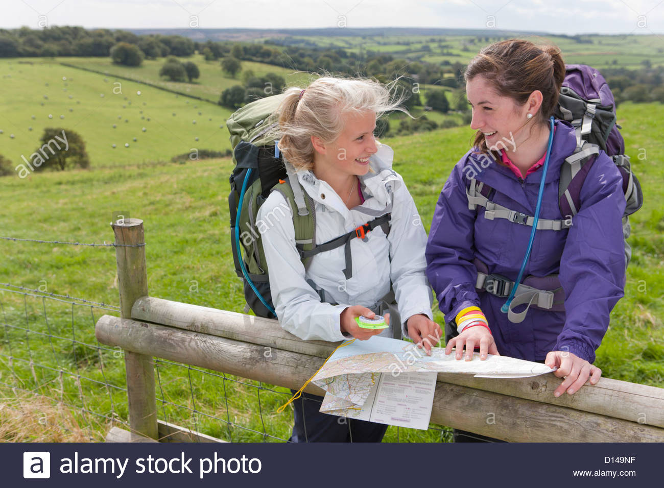 Smiling girls with backpacks compass and map against fence in field - Stock Image