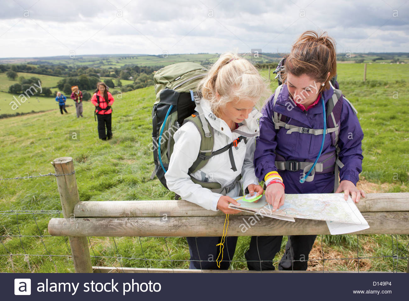 Girls with backpacks looking down at compass and map against fence in field Stock Photo