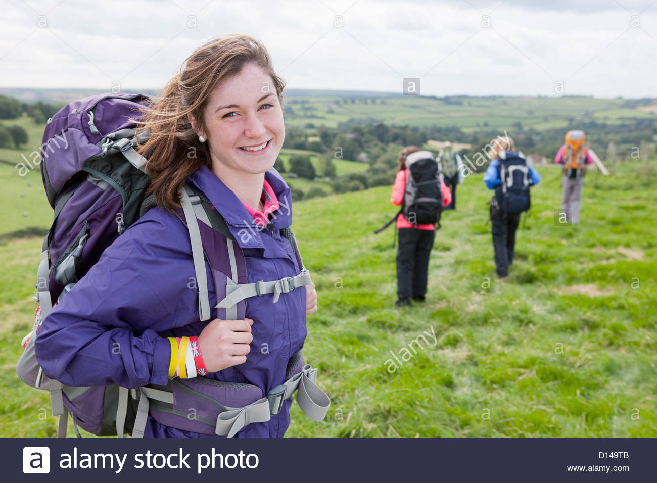 Portrait of smiling girl with backpack in field - Stock Image