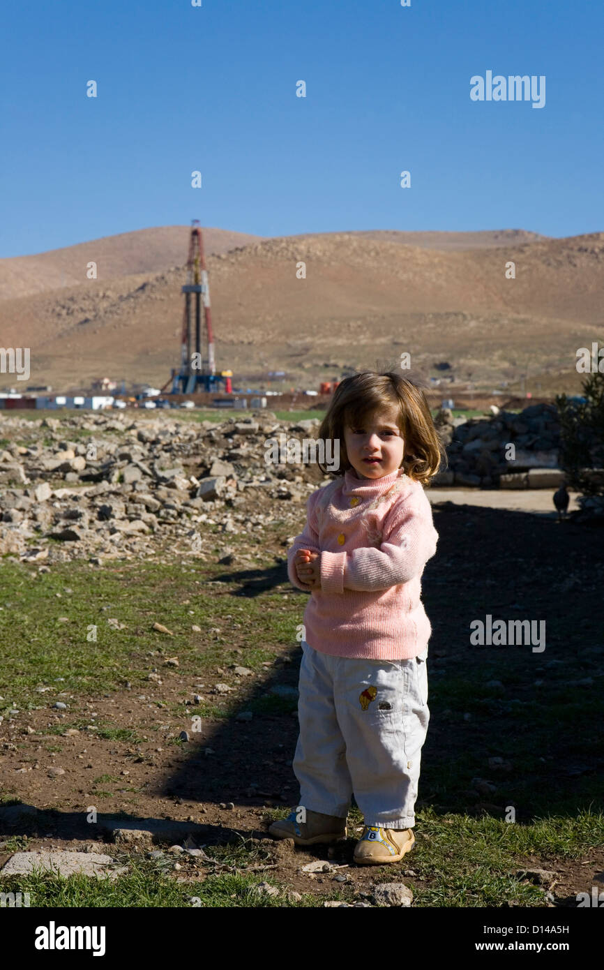 Kurdish refugee girl child toddler, near oil gas exploration rig, in mountainous region of Iraqi Kurdistan, Northern - Stock Image