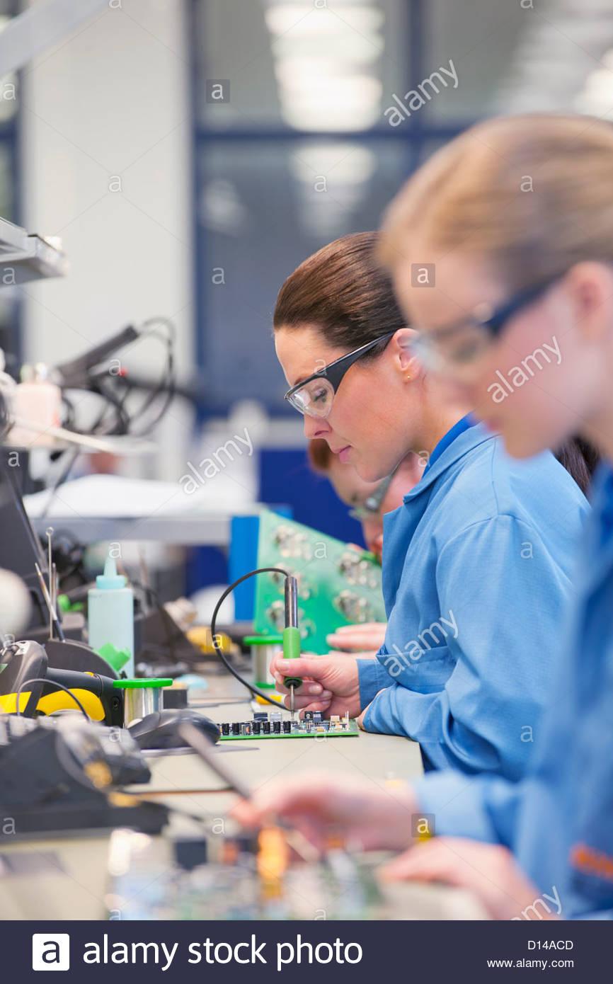 technicians soldering circuit boards on production line in stocktechnicians soldering circuit boards on production line in manufacturing plant