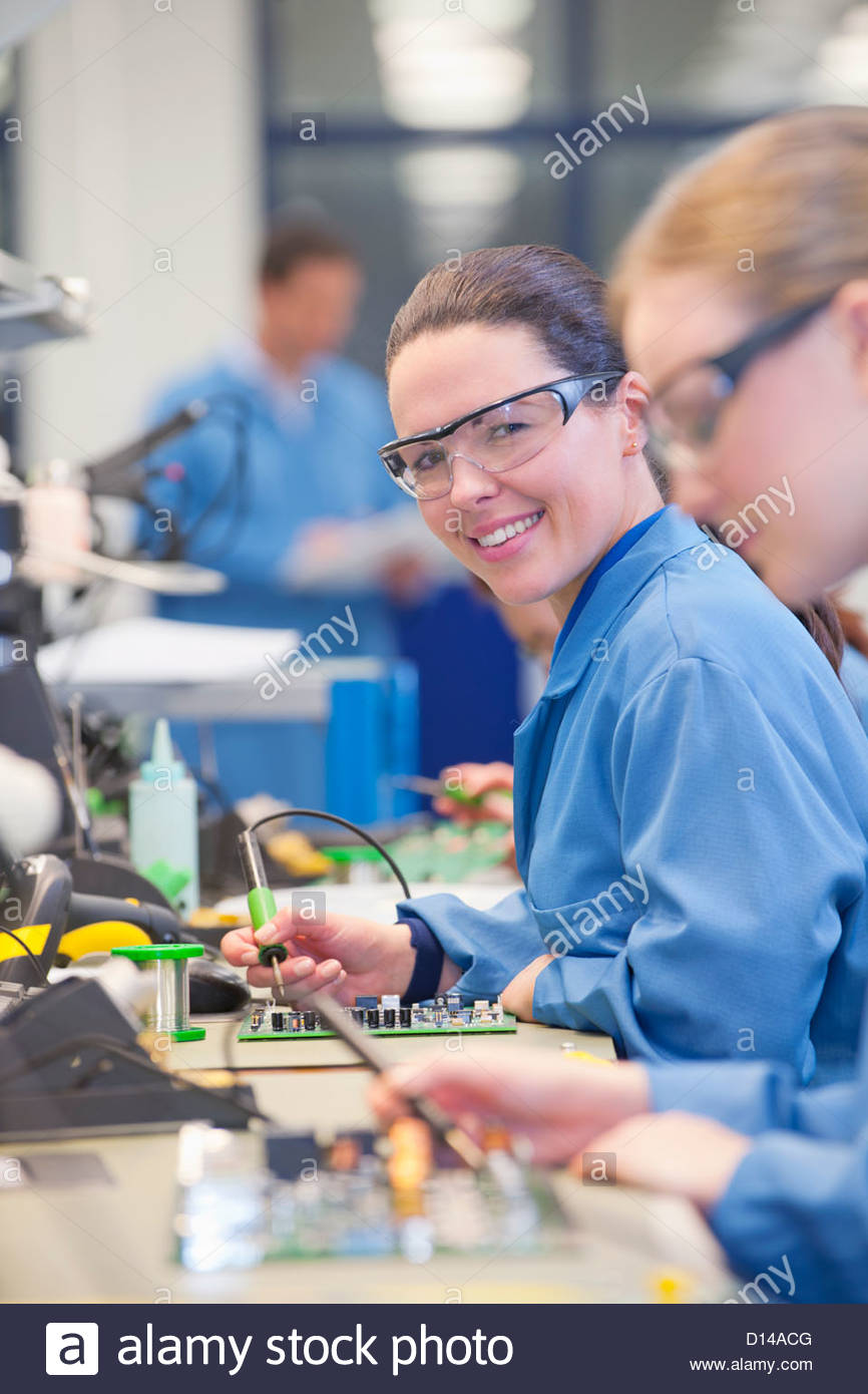 Portrait of smiling technician soldering circuit board on production line in manufacturing plant - Stock Image