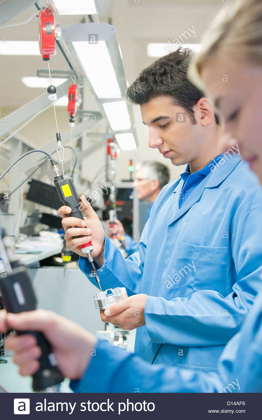 Technicians using electric screwdrivers to assemble machine parts on production line in manufacturing plant - Stock Image