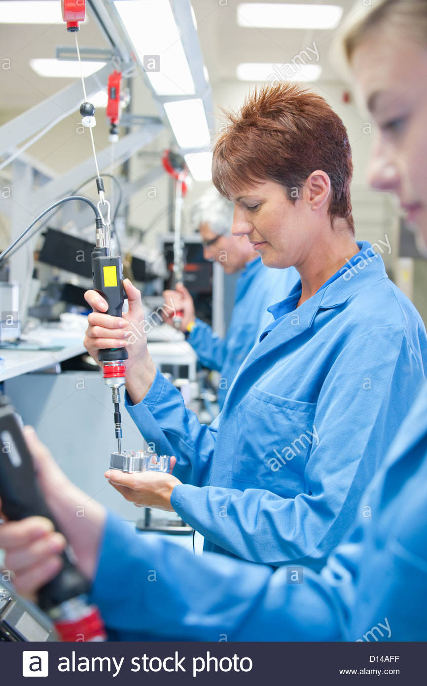 Technicians using electric screwdrivers to assemble machine parts in manufacturing plant - Stock Image