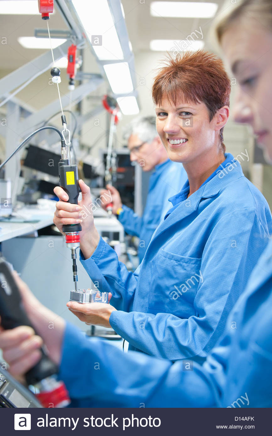 Portrait of smiling technician using electric screwdriver to assemble machine part in manufacturing plant - Stock Image