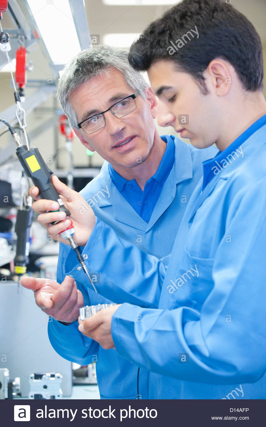 Supervisor training technician to use electric screwdriver to assemble machine part on production line in manufacturing - Stock Image